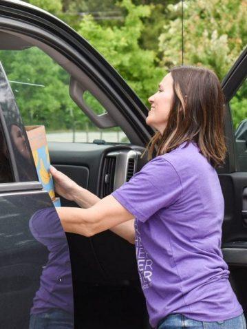Volunteer handing food to driver.